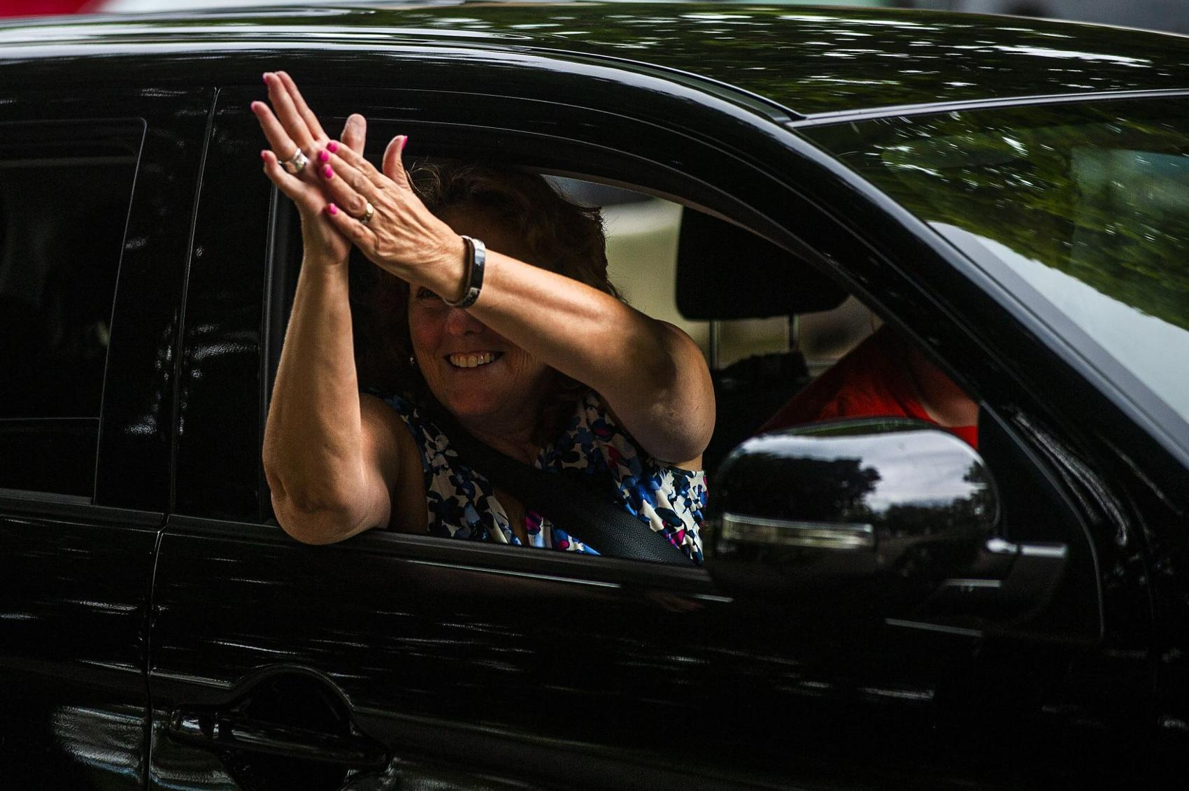 A participant applauds Art and Camille Taylor during a drive-by parade for the couple on Friday, July 31, 2020, in Bloomington. (Credit: Lewis Marien, The Pantagraph)