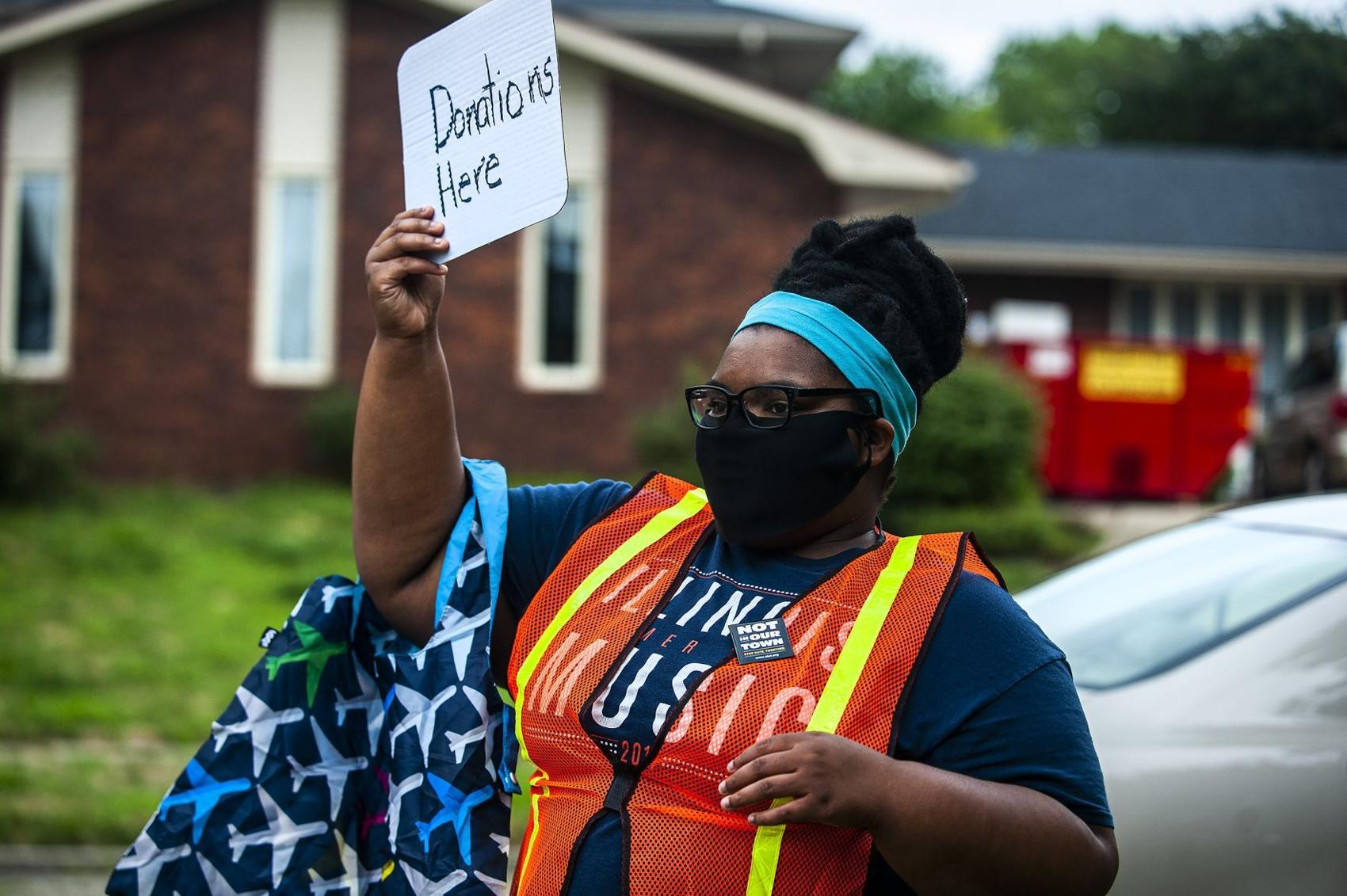 Ashyanna Watsonwaits to accept donations Friday, July 31, 2020, during a drive-by parade for Art Taylor and his wife, Camille, at their home in Bloomington. Donations would provide public schools resources to purchase more books normalizing diversity. (C