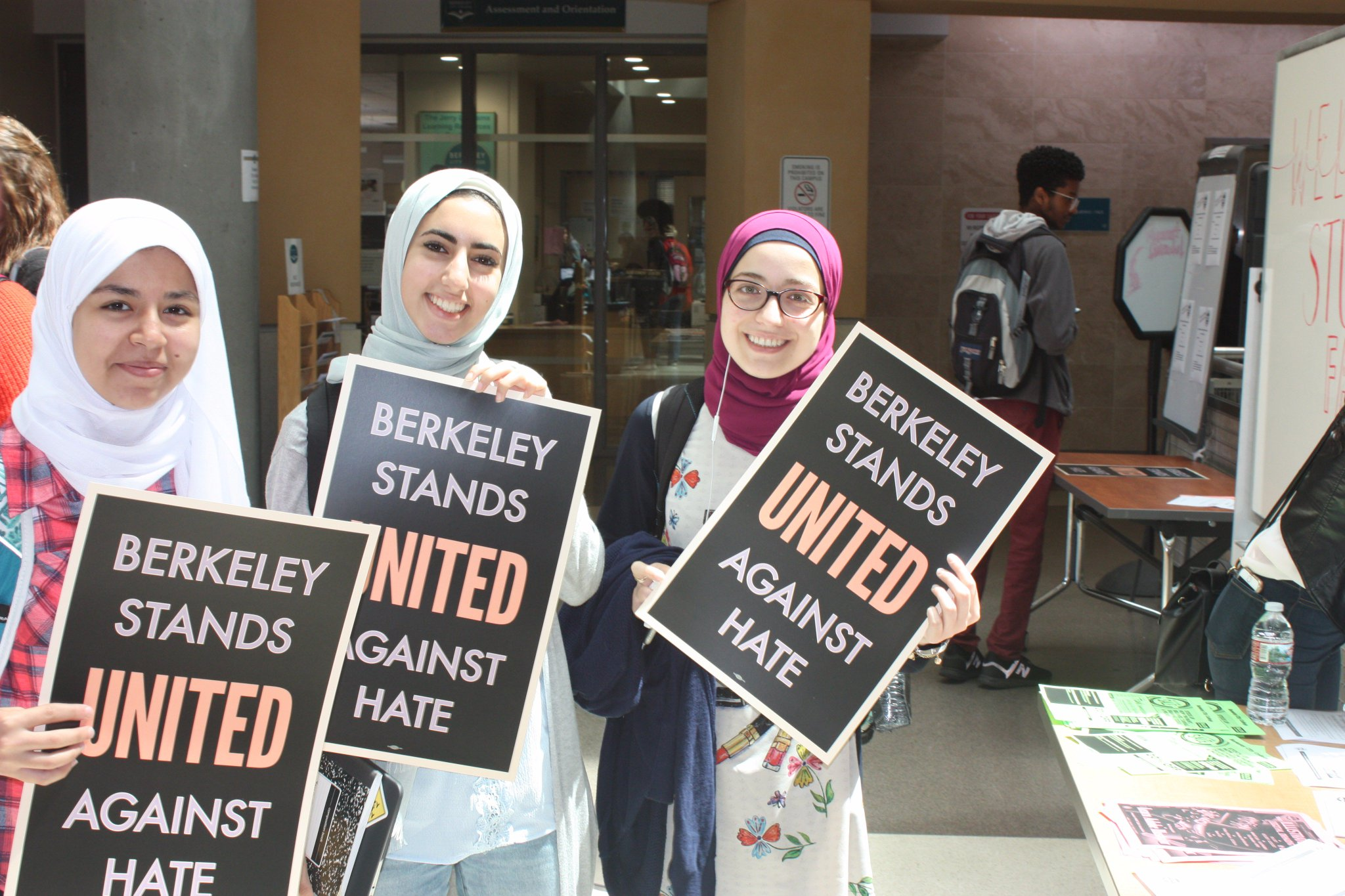 Three Muslim women holding 'Berkeley Stands United Against Hate' signs.