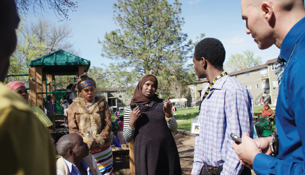 The Boise Police Department often holds information sessions at apartment complexes where many refugees live. Here, Saabo Ambar (center), who is originally from Somalia, discusses child safety laws with Dustin Robinson, Boise's refugee liaison officer (at far right). Pascal Sabima, of the International Rescue Committee, translates.
