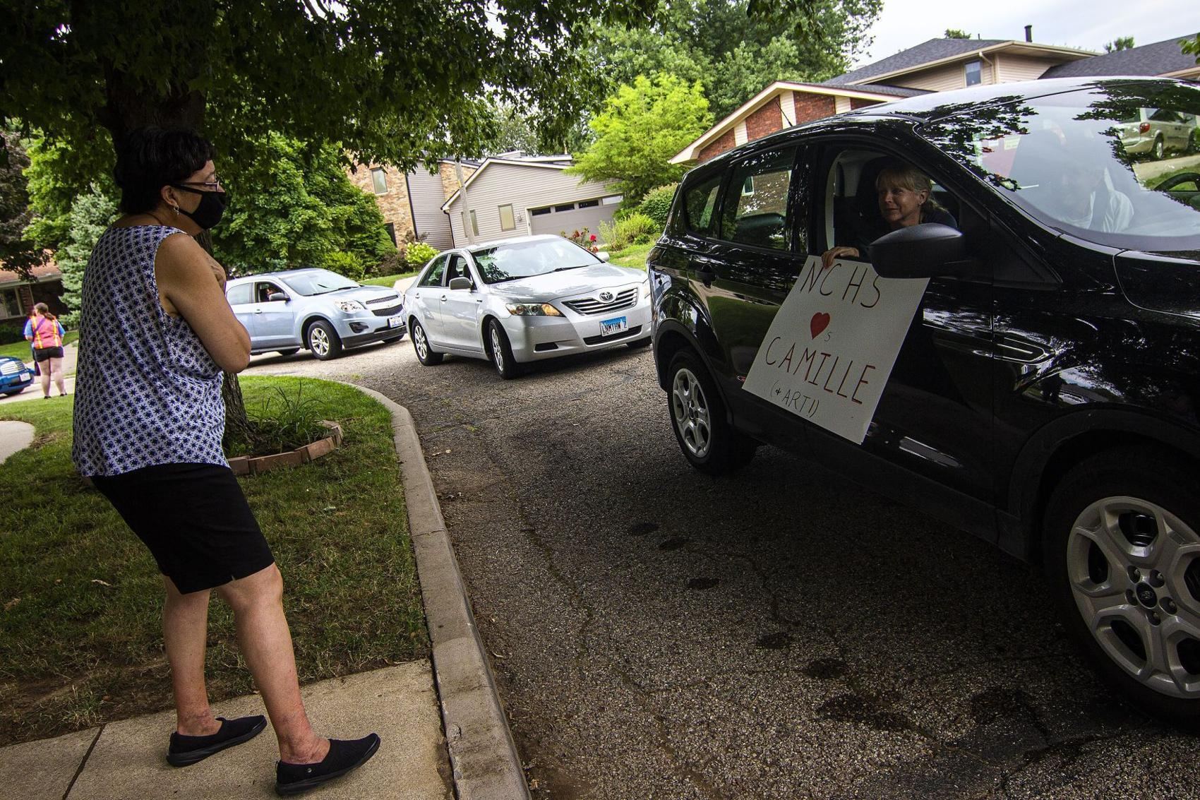 Camille Taylor greets a passerby during a drive-by parade for her and her husband, Art, on July 31 outside their home in Bloomington. (Credit: Lewis Marien, The Pantagraph)