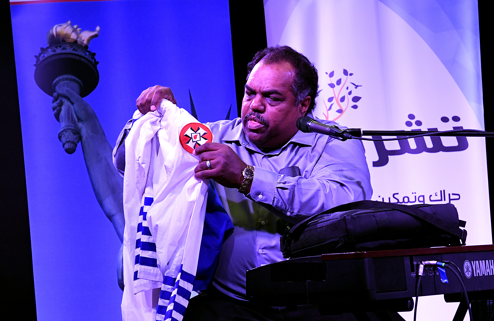 Daryl Davis holding up KKK robes at Blues and Rock for Humanity in November 2017. © Wikipedia / Creative Commons