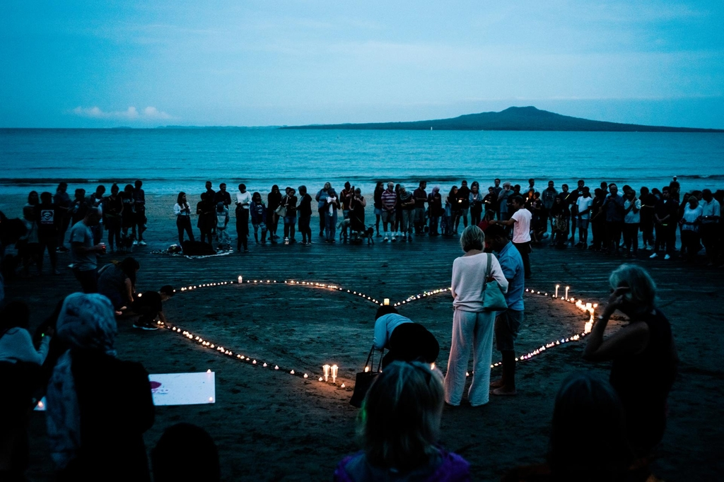 Crowds gather for a vigil on Takapuna beach Auckland. Getty Images