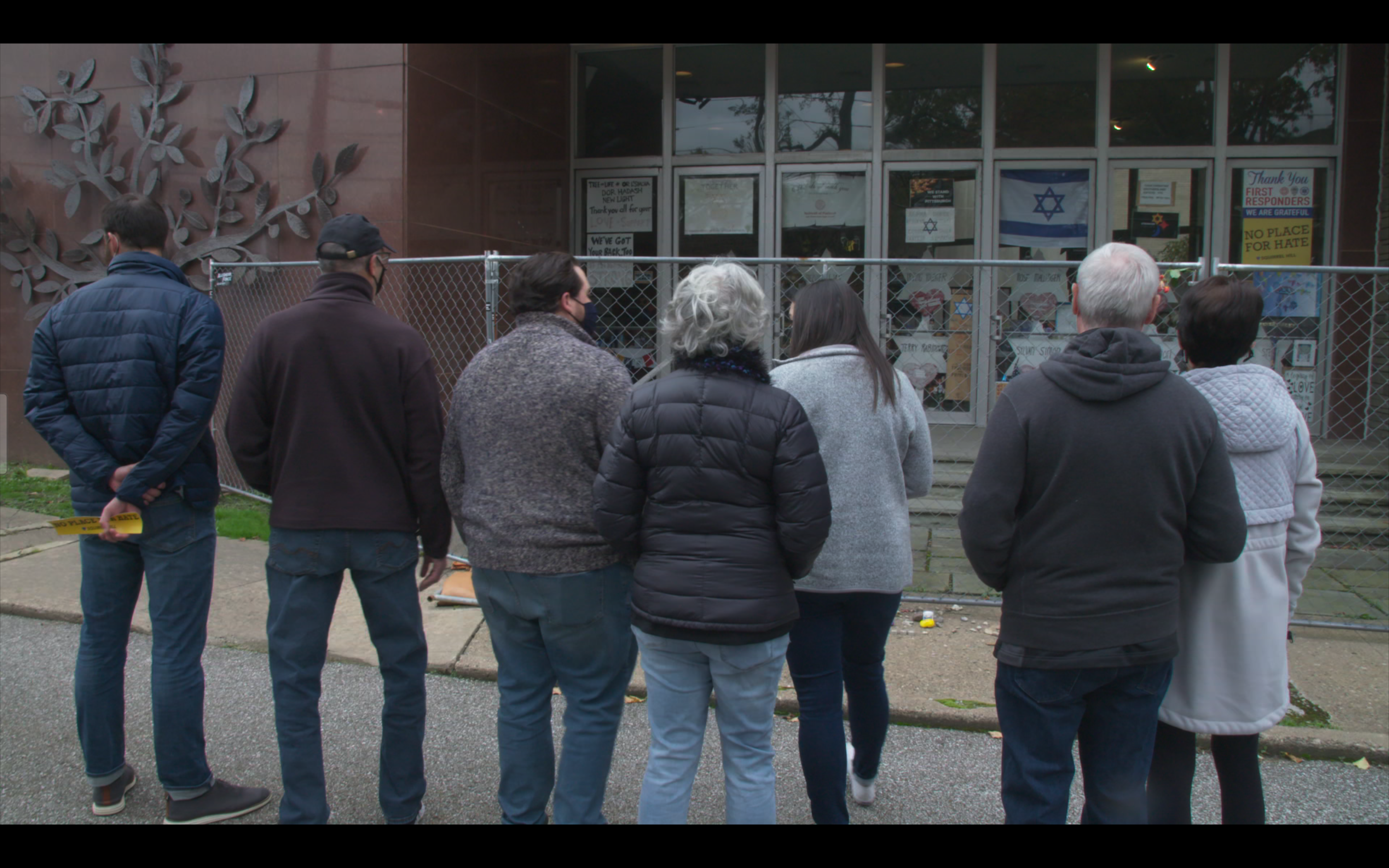 Family members look at the makeshift memorial in the windows that remember those lost at the Tree of Life Synagogue.