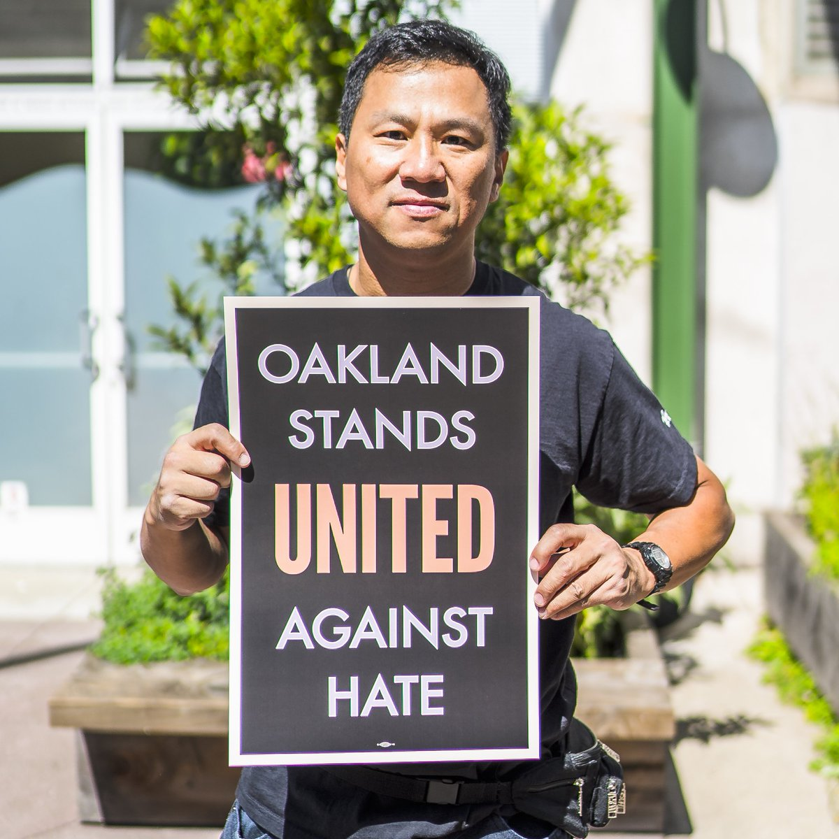 Twitter photo of East Bay resident holding 'Stand Against Hate' sign.