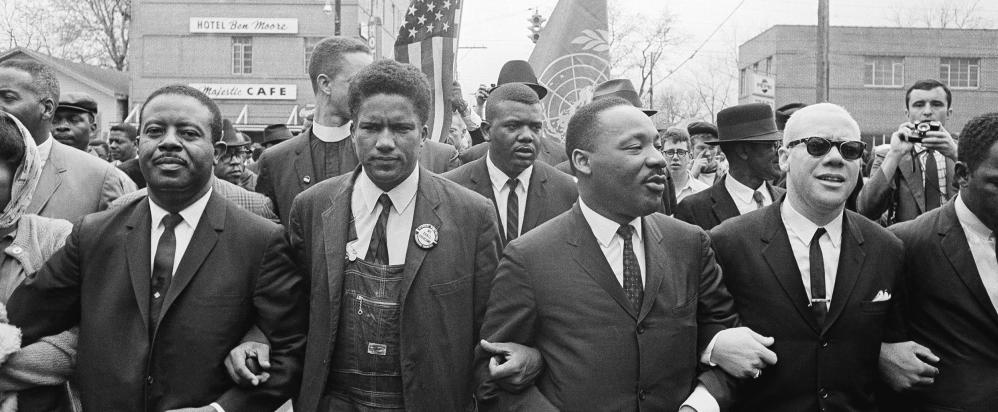 Dr. Martin Luther King, Jr. locks arms with his aides as he leads a march of several thousands on March 17, 1965 in Montgomery, Ala. (Credit: AP)