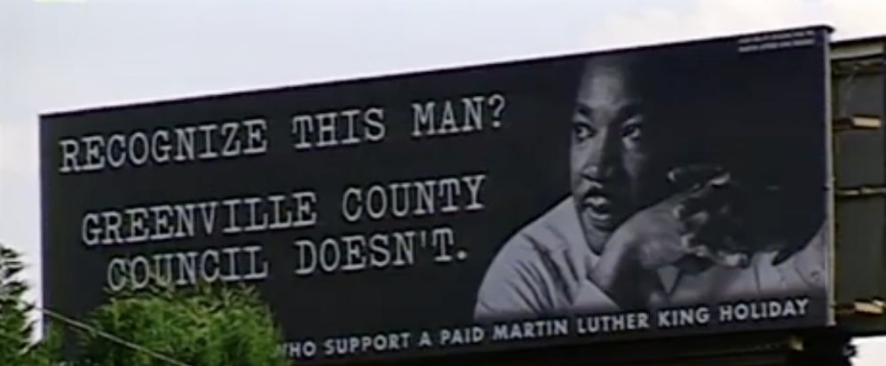 A sign by the side of the road paid for by community members who supported a Martin Luther King Jr. Holiday in Greenville County. (Credit: NIOT 'Holiday' film, 2003)