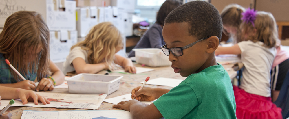 Captured in a metropolitan Atlanta, Georgia primary school, seated amongst his classmates, this photograph depicts a young African-American schoolboy drawing. (Credit: CDC on Unsplash)
