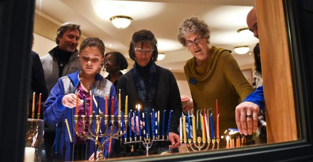 People light menorahs next to a window during the 25th anniversary of Not In Our Town at Congregation Beth Aaron in Billings, MT earlier this year. (Photo: Ryan Welch, Billings Gazette)