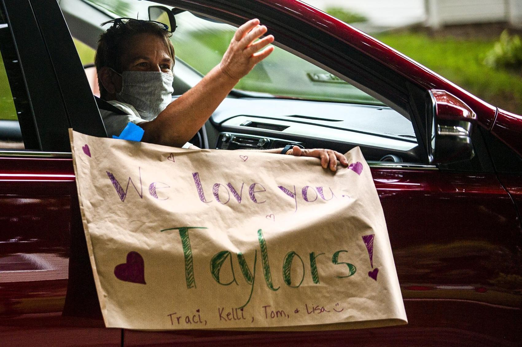 A participant shows love during a drive-by parade for Art and Camille Taylor on Friday, July 31, 2020, in Bloomington. (Credit: Lewis Marien, The Pantagraph)