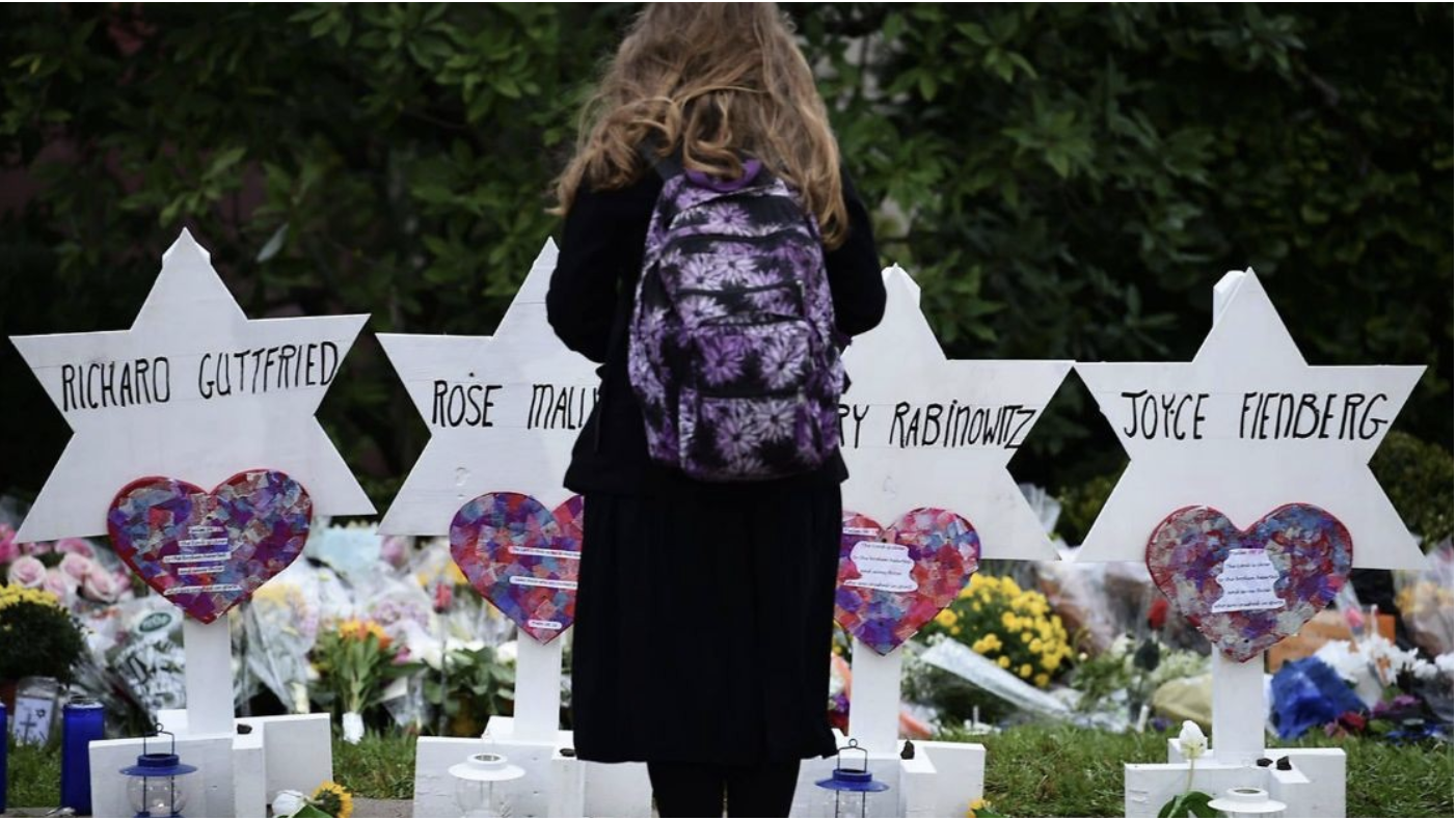 A young girl pauses to pray in front of the Tree of Life Synagogue memorial